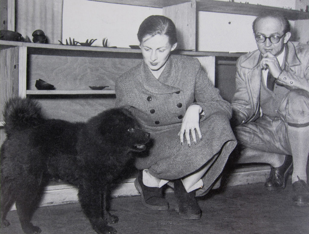 Herta Baller Petting a Fluffy Dog with Hans Waldstätten in Walter Bosse's Shop